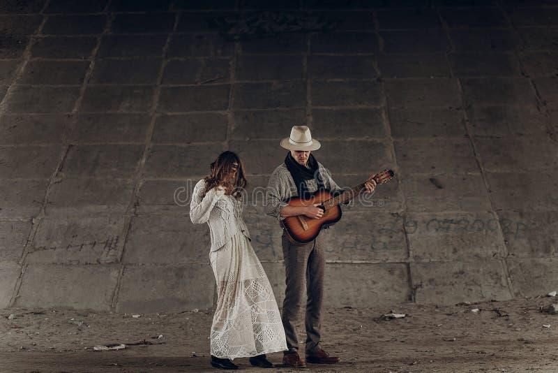 La femme gitane élégante dans le boho vêtx la danse près de l'homme bel, c photo libre de droits
