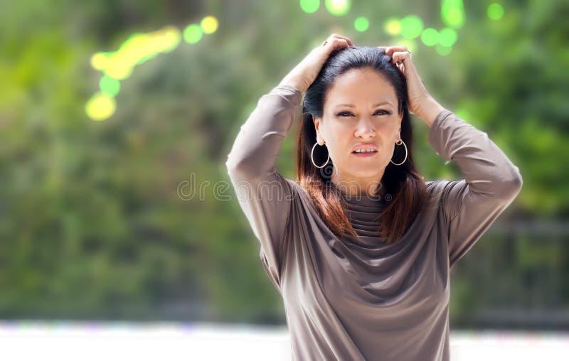 La femme habillée dans argent-gris détend par la piscine images libres de droits