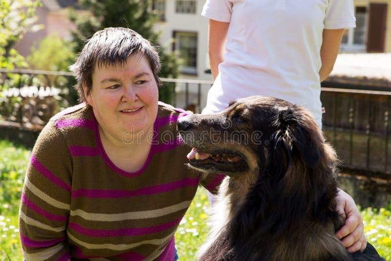 La femme handicapée est caresse par chien photos libres de droits