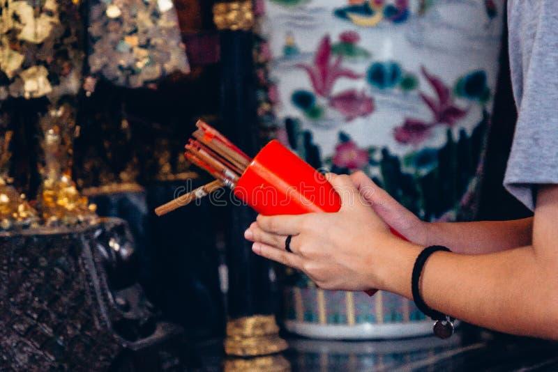 La femme haute étroite de mains doit secouer des bâtons de Chi-Chi ou Couture-SI au temple thaïlandais, un du bâton est fortune e photos libres de droits