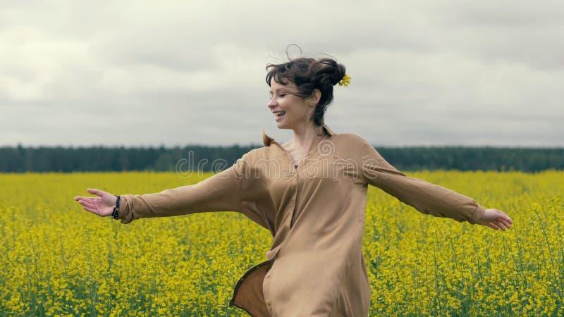 La femme heureuse apprécie une promenade d'été dans le domaine Fleurs de jaune de champ d'été photographie stock