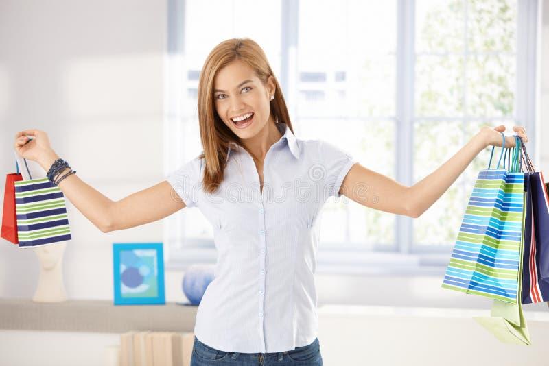 La femme heureuse arme les sacs à provisions grands ouverts de fixation image stock
