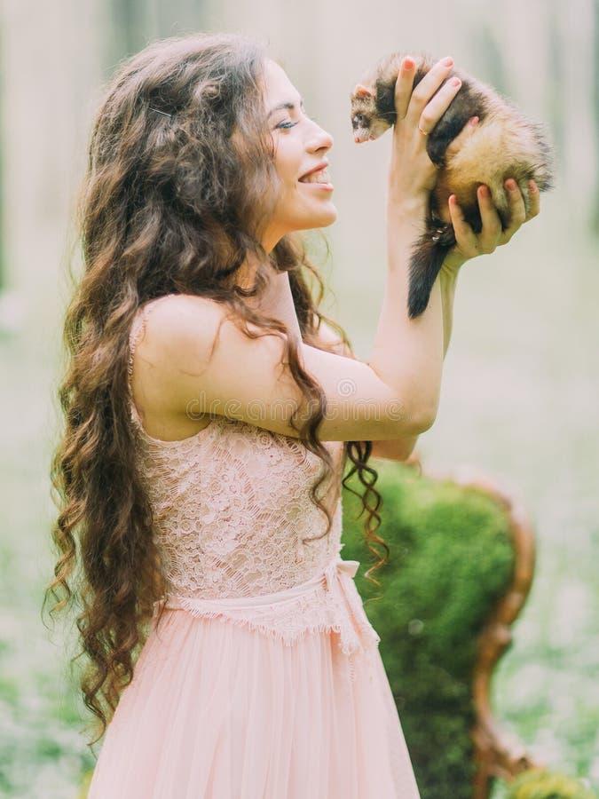 La femme heureuse avec de longs cheveux bouclés dans l'exploitation rose-clair de robe, choyant et jouant avec le furet en vert photo stock