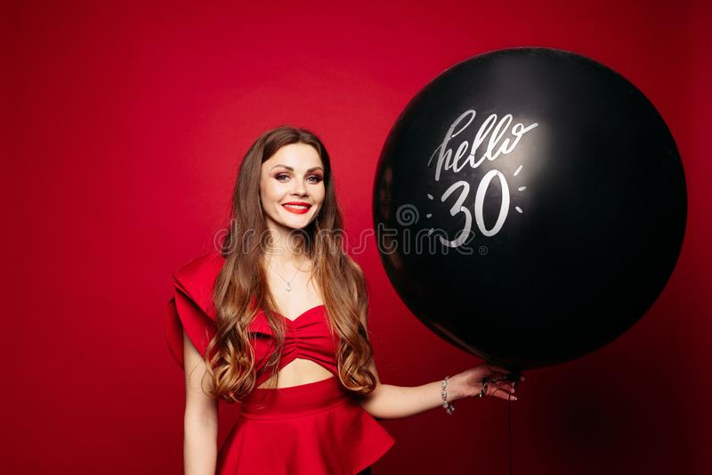 La femme heureuse avec le ballon à air noir dit bonjour 30 sur le fond rouge images stock