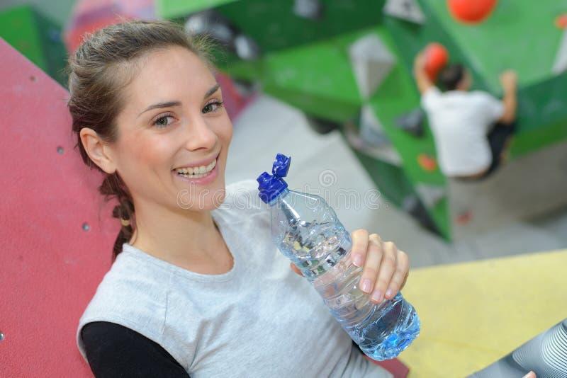 La femme heureuse boit l'eau et se repose au centre s'élevant de mur image stock