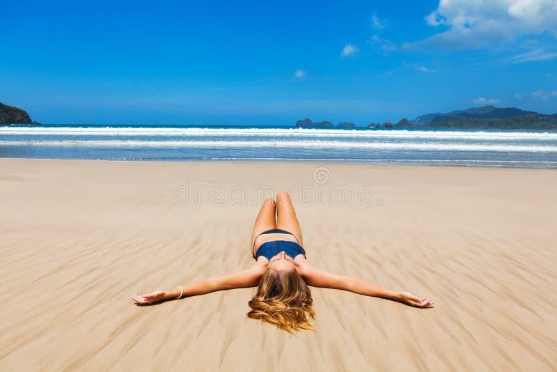 La femme heureuse dans le bikini détendent, ont plaisir à les prendre un bain de soleil sur la plage de sable photos stock