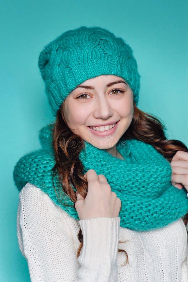 La femme heureuse dans une turquoise a tricoté le chapeau dans le studio image libre de droits