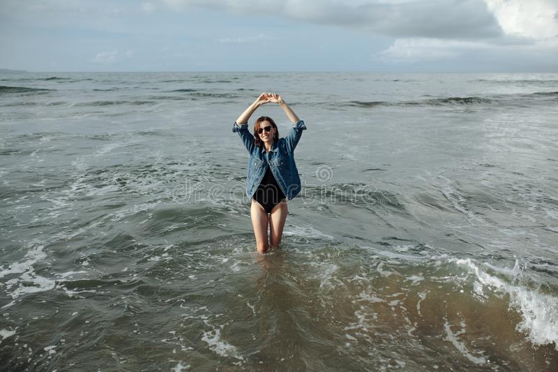 La femme heureuse de brune de sourire utilisant la veste noire de maillot de bain et de denim au fond d'océan ont plaisir à march images stock