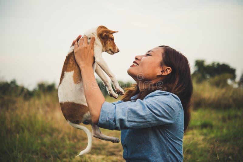 La femme heureuse de hippie sourit et tient un petit chien Petit chiot W images stock