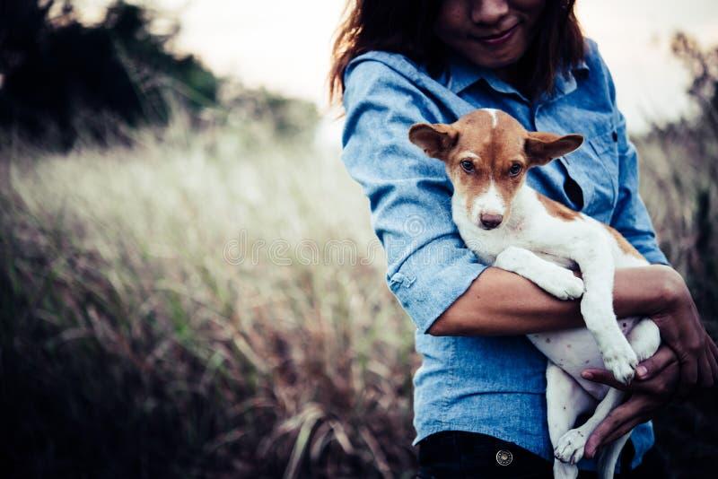 La femme heureuse de hippie sourit et tient un petit chien Petit chiot W images libres de droits