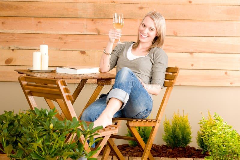 La femme heureuse de jardin apprécient la terrasse en verre de vin photo stock