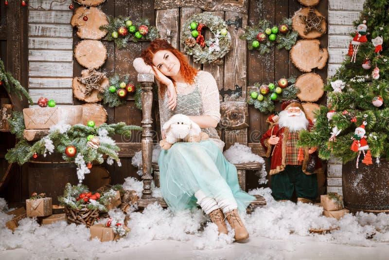 La femme heureuse de Noël posant dans l'arbre de sapin avec l'hiver de nouvelle année de boîte-cadeau a décoré le fond photos stock