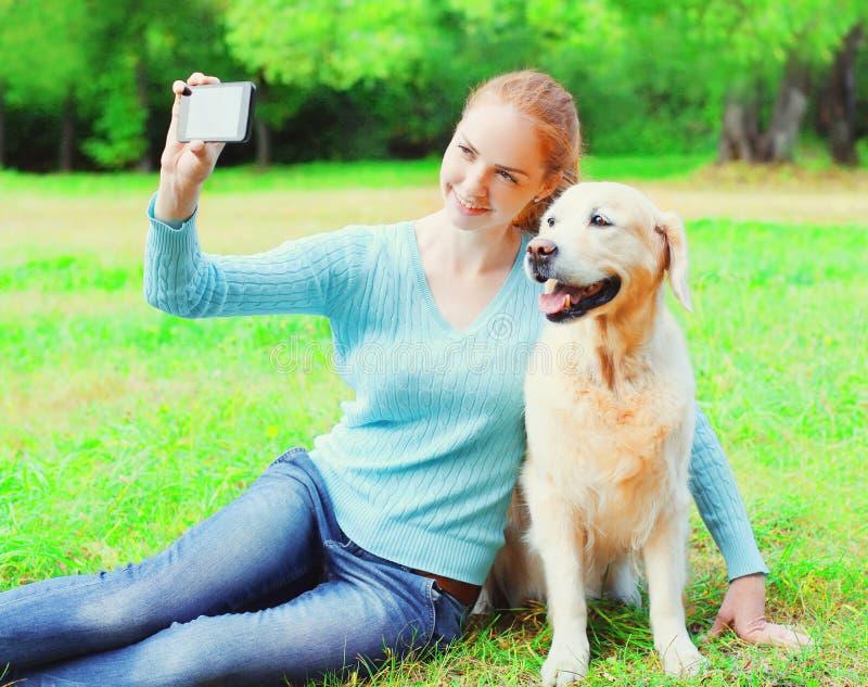 La femme heureuse de propriétaire avec le chien de golden retriever prend le portrait de selfie de photo sur un smartphone le jou photo libre de droits