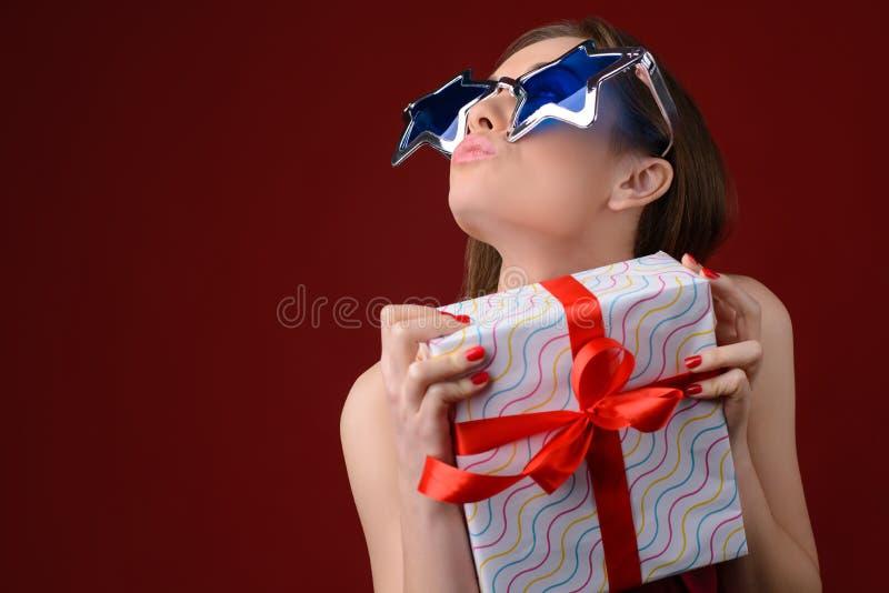 La femme heureuse drôle dans le grand envoi de lunettes de soleil s'embrassent et se tenir image libre de droits