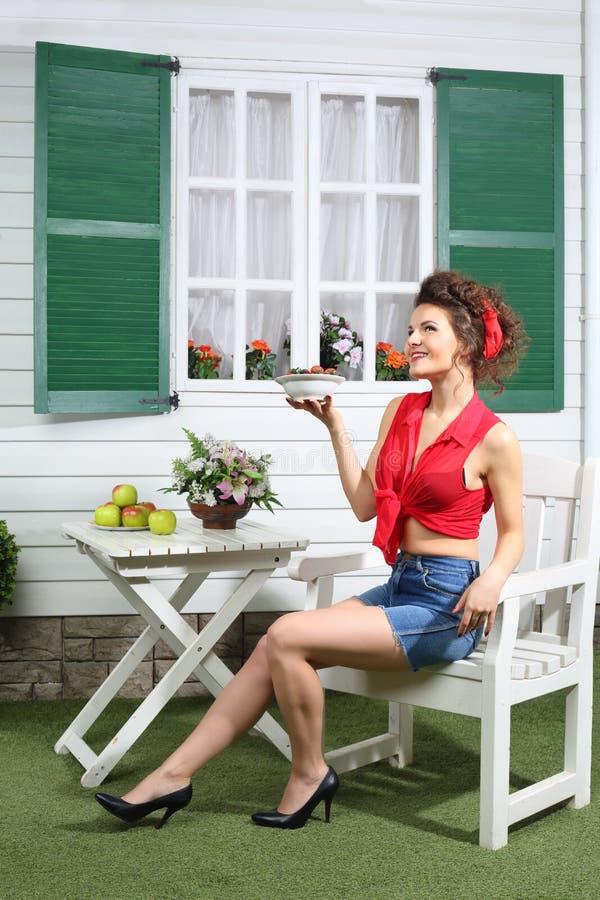La femme heureuse en bref s'assied à la prochaine maison de campagne de table photos stock
