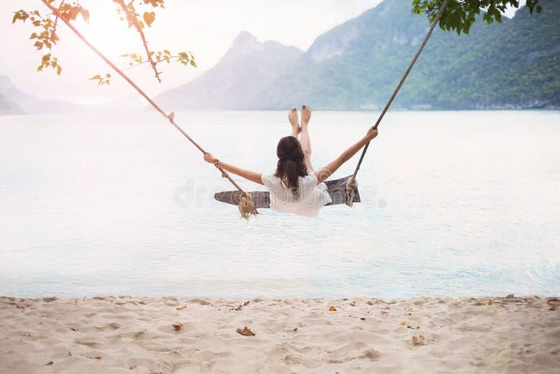 La femme heureuse insouciante sur l'oscillation sur de beaux paradis échouent photographie stock libre de droits