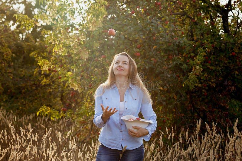 la femme 45 heureuse an jette une pomme dans le jardin d'automne au coucher du soleil image libre de droits