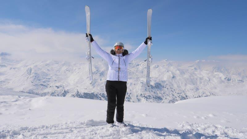 La femme heureuse l'élève les skis inclinés sur le sommet de montagne photographie stock libre de droits
