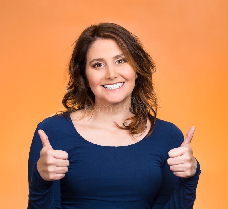 La femme heureuse montrant des pouces lèvent le geste images stock