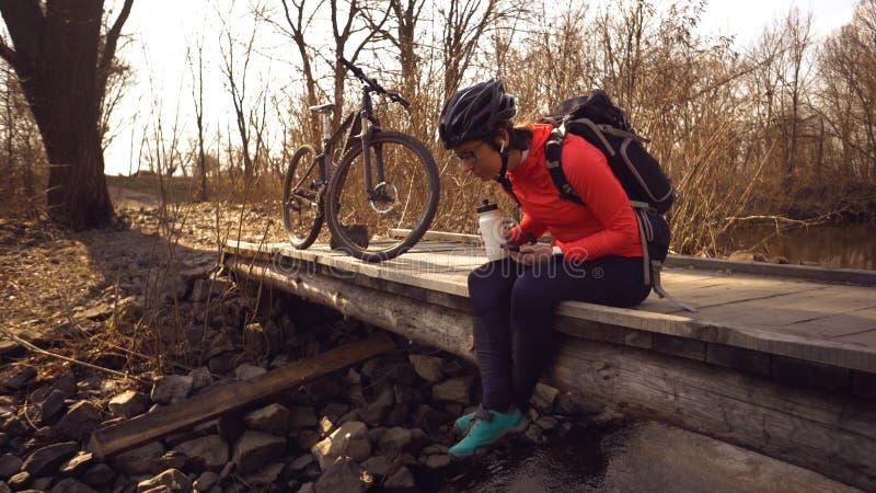 La femme heureuse repose le pont en bois au-dessus de la rivi?re, musique de ?coute dans des ?couteurs avec des mains de smartpho photos stock