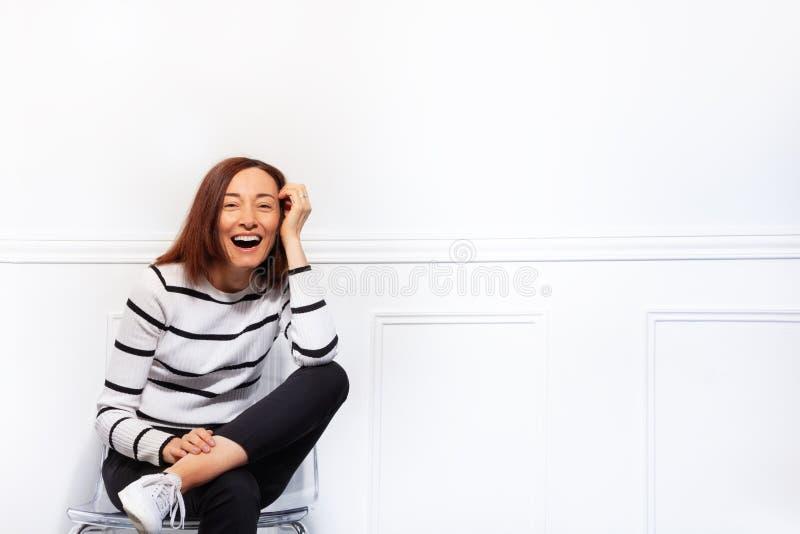 La femme heureuse s'asseyant sur la chaise avec des jambes a croisé photographie stock