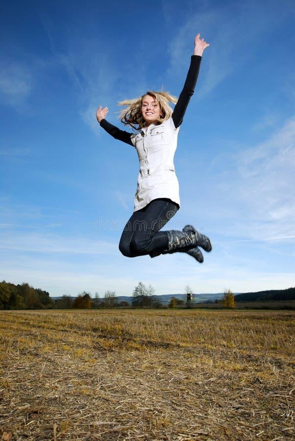 La femme heureuse saute images stock