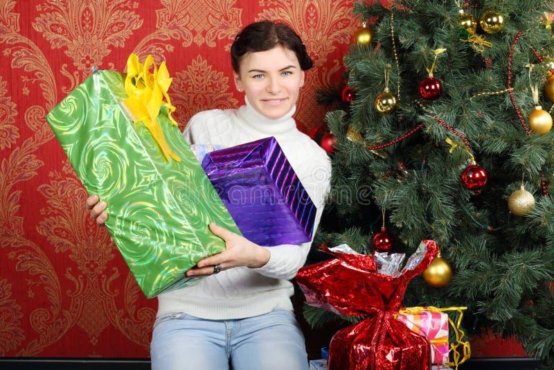 La femme heureuse tient beaucoup de cadeaux près de l'arbre de Noël photographie stock libre de droits