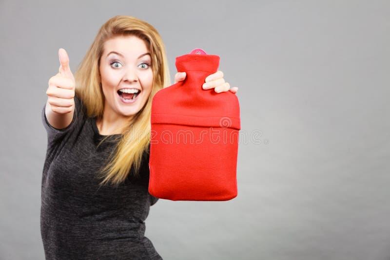 La femme heureuse tient la bouteille d'eau chaude image stock