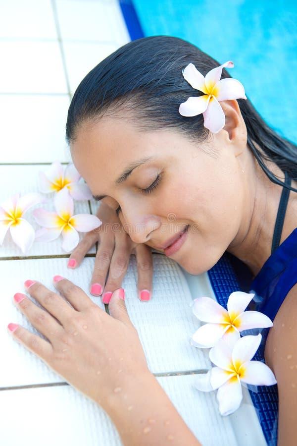 La femme hispanique avec de longs cheveux noirs, observe la détente fermée par la piscine photos stock