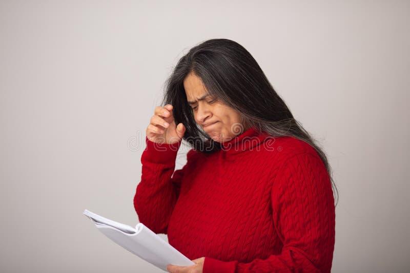La femme hispanique regarde pensivement le carnet photos libres de droits