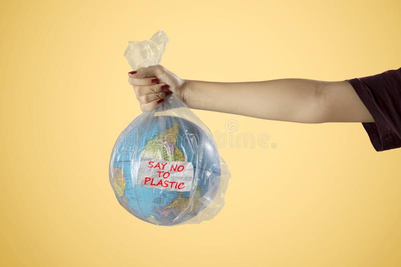 La femme inconnue tient le sachet en plastique et le globe de la terre photo libre de droits