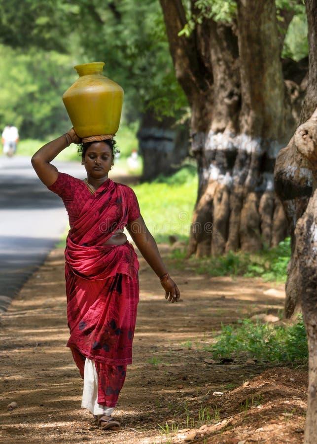 La femme indienne porte le pot de l'eau sur sa tête. photo stock
