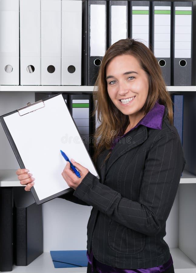 La femme indique un presse-papiers avec un stylo photos stock