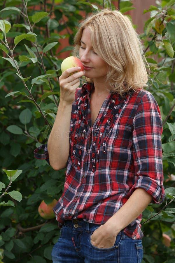 La femme inhale l'arome d'une pomme photo stock