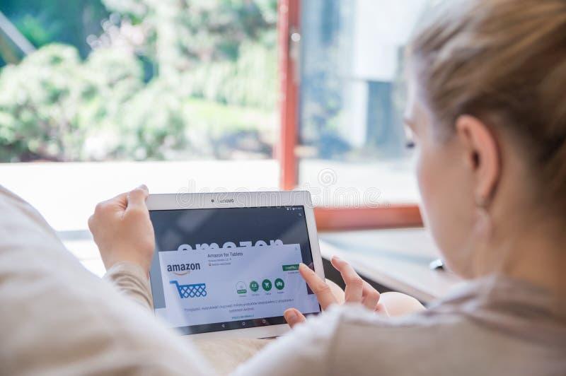 La femme installe l'application d'Amazone sur le comprimé de Lenovo images stock