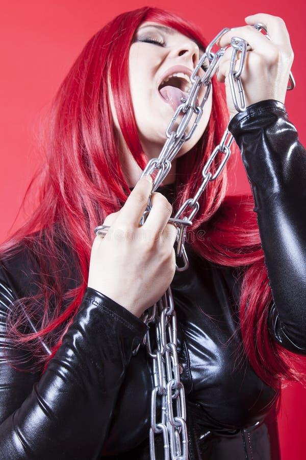 La femme lèche la chaîne en acier image stock