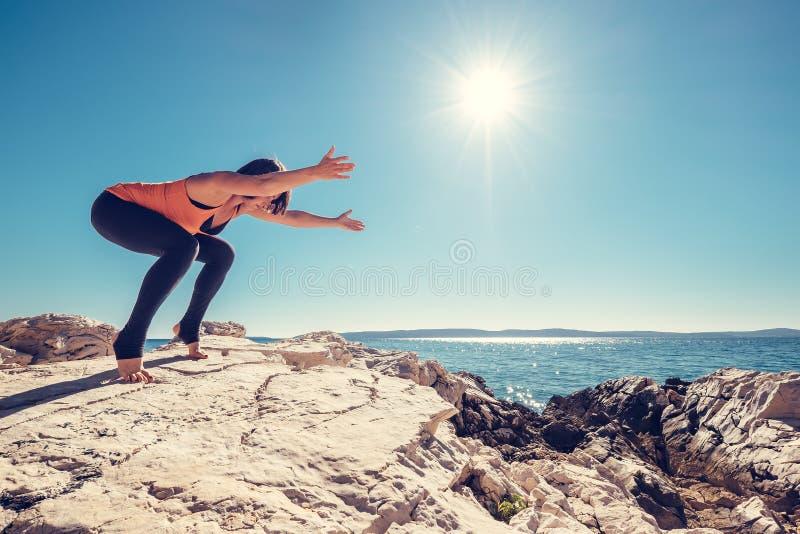 La femme a la pratique en matière de yoga sur la côte abandonnée image stock