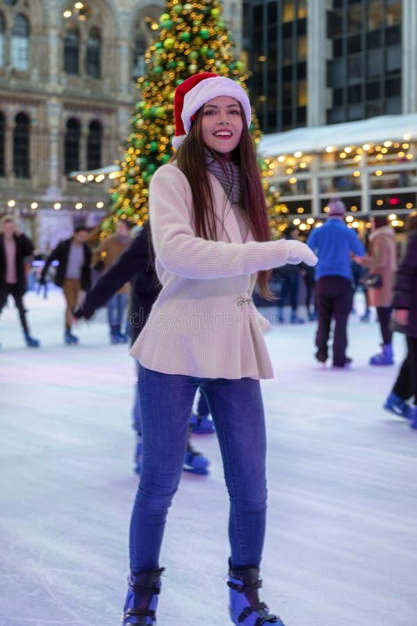La femme a le patinage de glace d'amusement sur un marché de Noël images stock