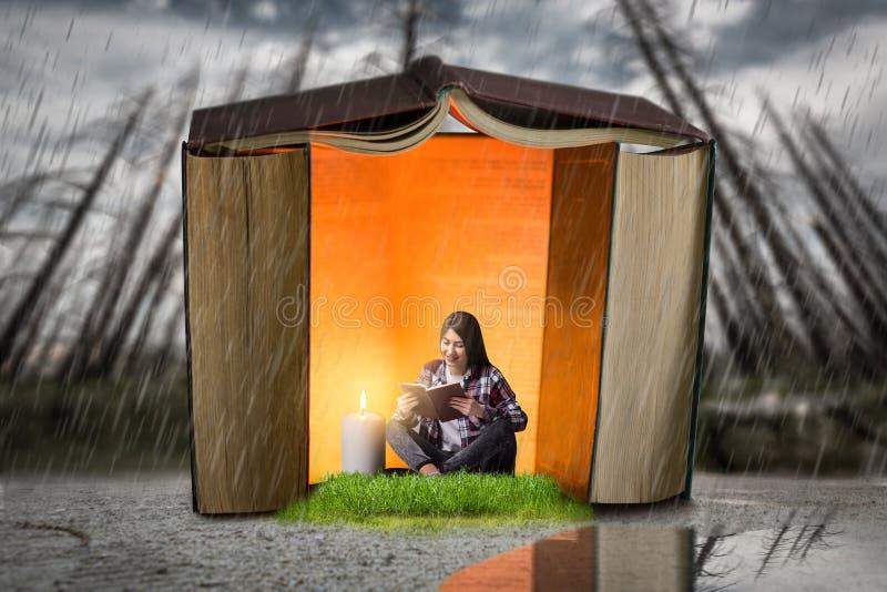 La femme lit dedans la maison construite des livres photo stock