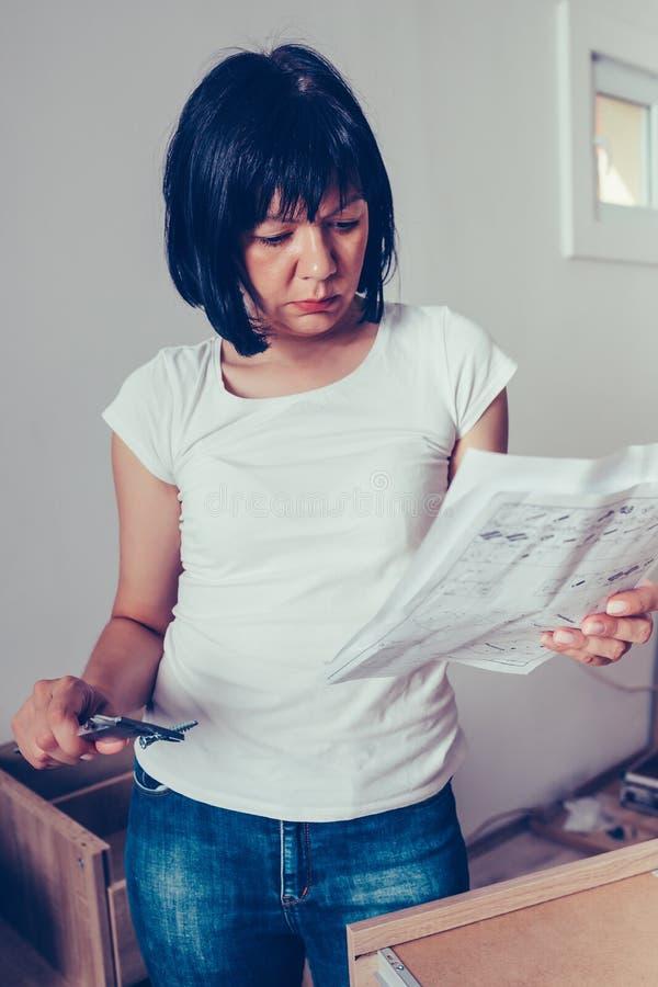 La femme lit l'instruction pour des meubles d'installation et vérifie la taille de vis avec le calibre photo libre de droits