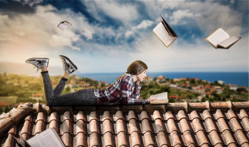 La femme lit tout en se trouvant sur le dessus du toit image libre de droits