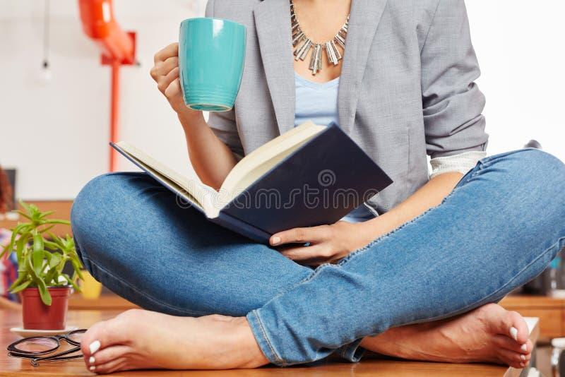 La femme lit un livre dans sa pause-café image libre de droits