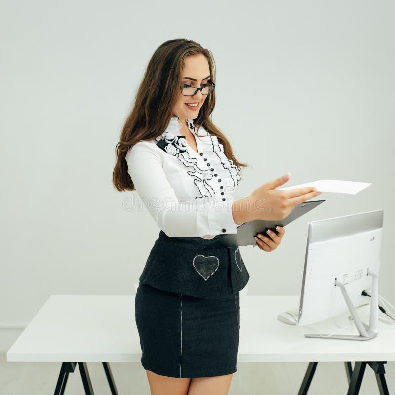 La femme a lu un rapport dans le bureau images libres de droits