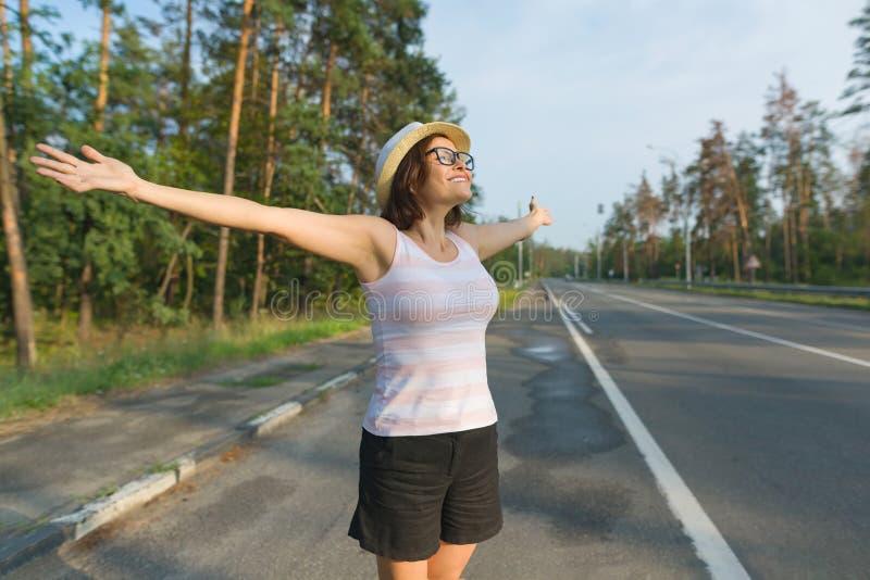 La femme mûre de sourire se tient sur la route, a étendu ses bras aux côtés, appréciant la liberté et le coucher du soleil photographie stock