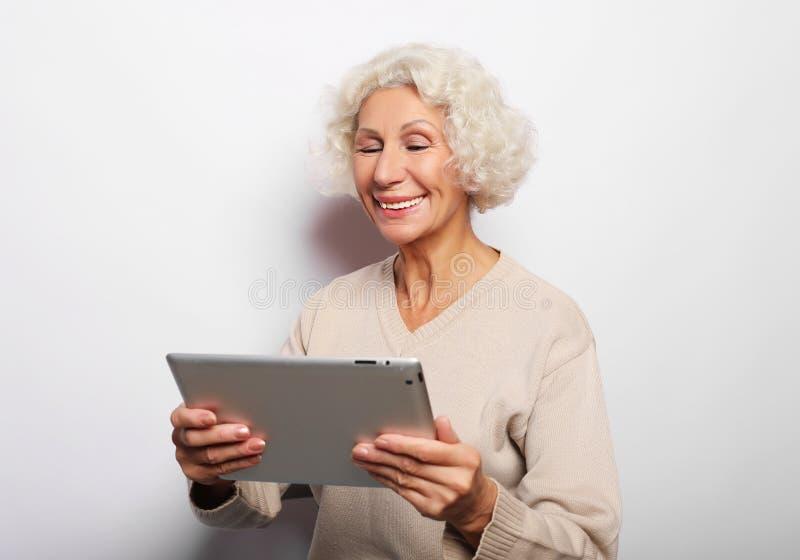La femme mûre heureuse à l'aide d'un comprimé, communique avec des enfants et des petits-enfants photographie stock libre de droits