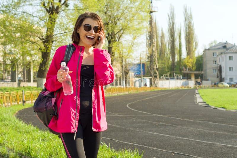 La femme mûre sportive de portrait au stade, dans les sports vêtx pour former, avec la bouteille de l'eau, parlant au téléphone photos libres de droits