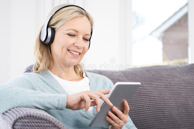 La femme mûre coule la musique de la Tablette de Digital à Headp sans fil photos libres de droits