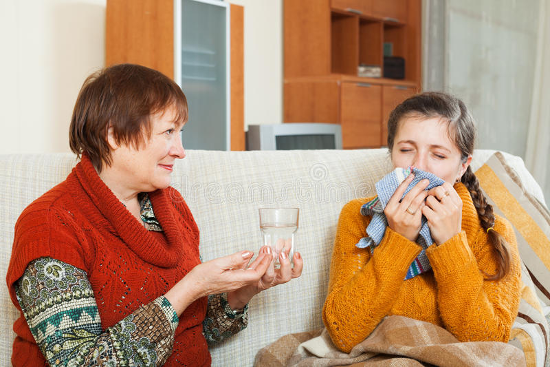La femme mûre s'occupant de sa fille adulte a la toux photographie stock