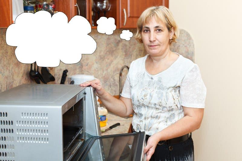 La femme mûre se tenant dans la cuisine près a ouvert le fourneau photographie stock