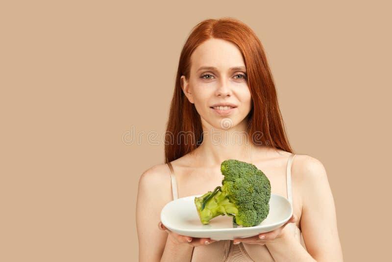 La femme maigre dans les sous-vêtements tenant le brocoli, léchant, veut le manger beaucoup photographie stock